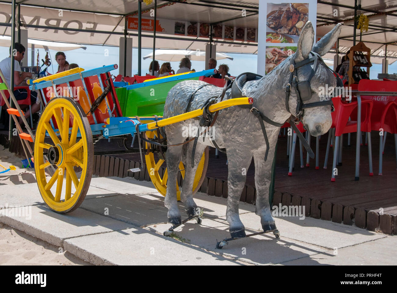 Little Grey Donkey and Colourful Cart Advertising Model novelty fibreglass model of little grey portuguese donkey standing between the shafts of red g Stock Photo