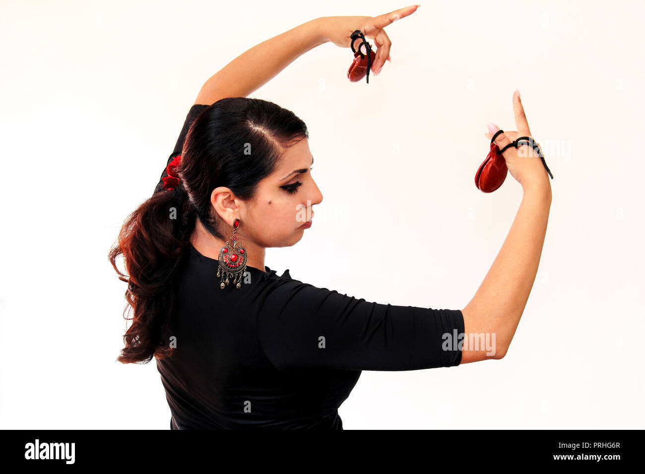 Young Spanish gipsy woman dancing flamenco with brown castanets in her hands. Flamenco dancer in beautiful national dress on a white background. Spain - Stock Image