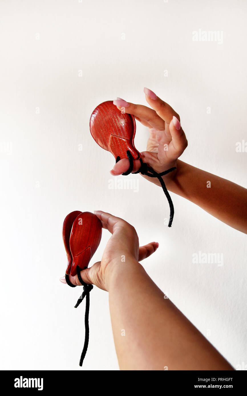 Spanish castanets in the hands on white background, close up. Percussion instrument used in flamenco, sevillanas dance in Spain, isolated, close up. - Stock Image