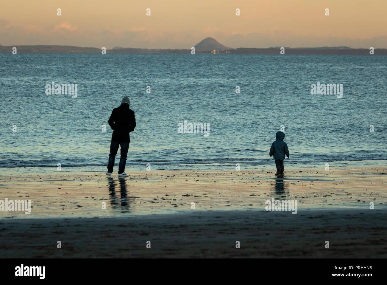 Father and son walking on Portobello Beach Edinburgh, Scotland - Stock Image