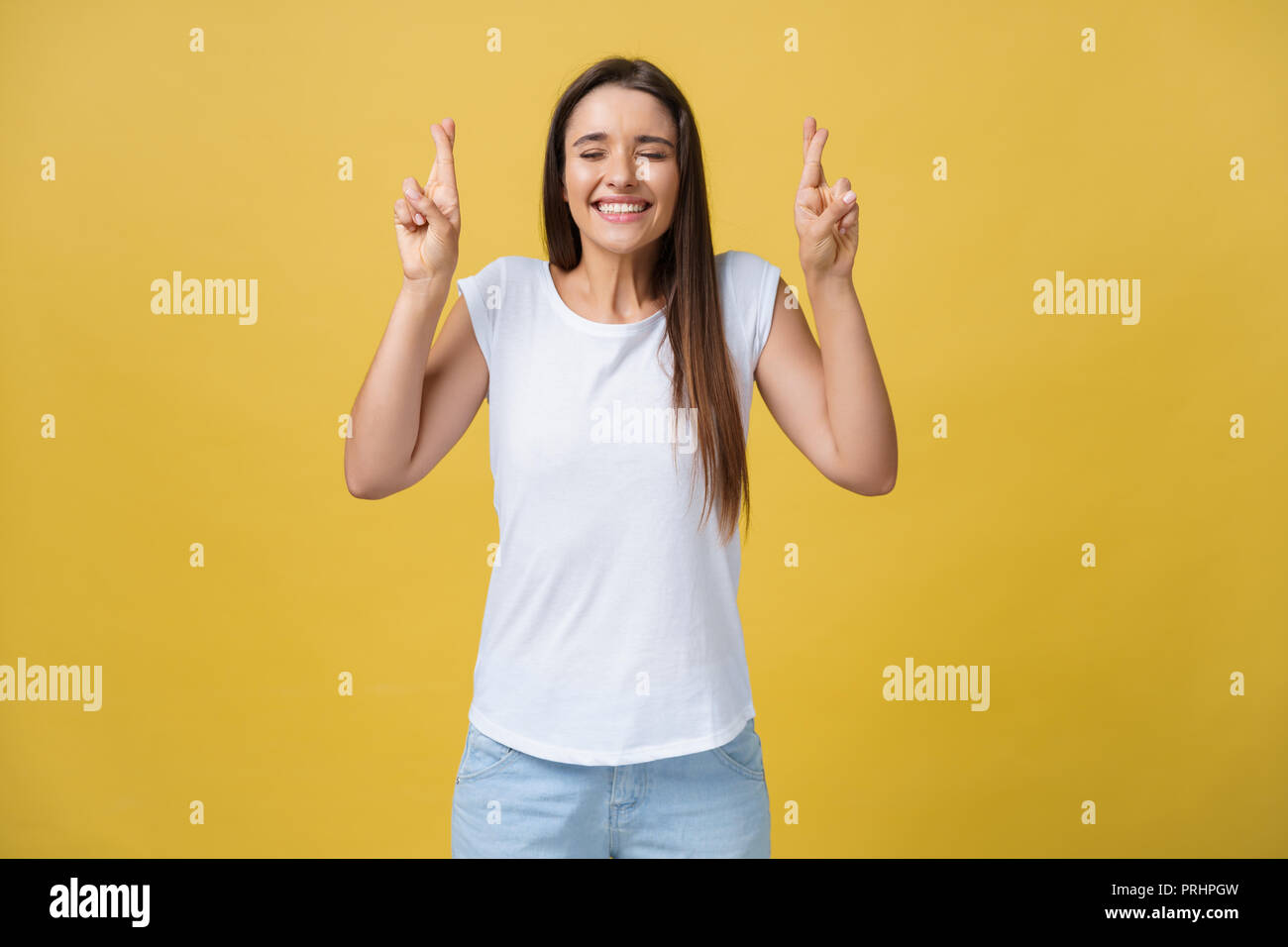 Intrigued woman in t-shirt praying with crossed fingers and looking away over yellow background - Stock Image