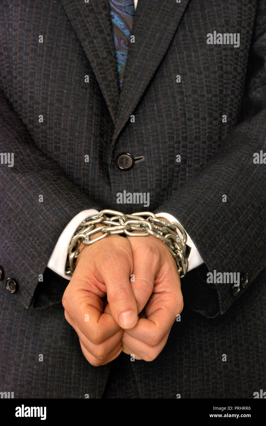 man in suit with hands tied with a chain - Stock Image