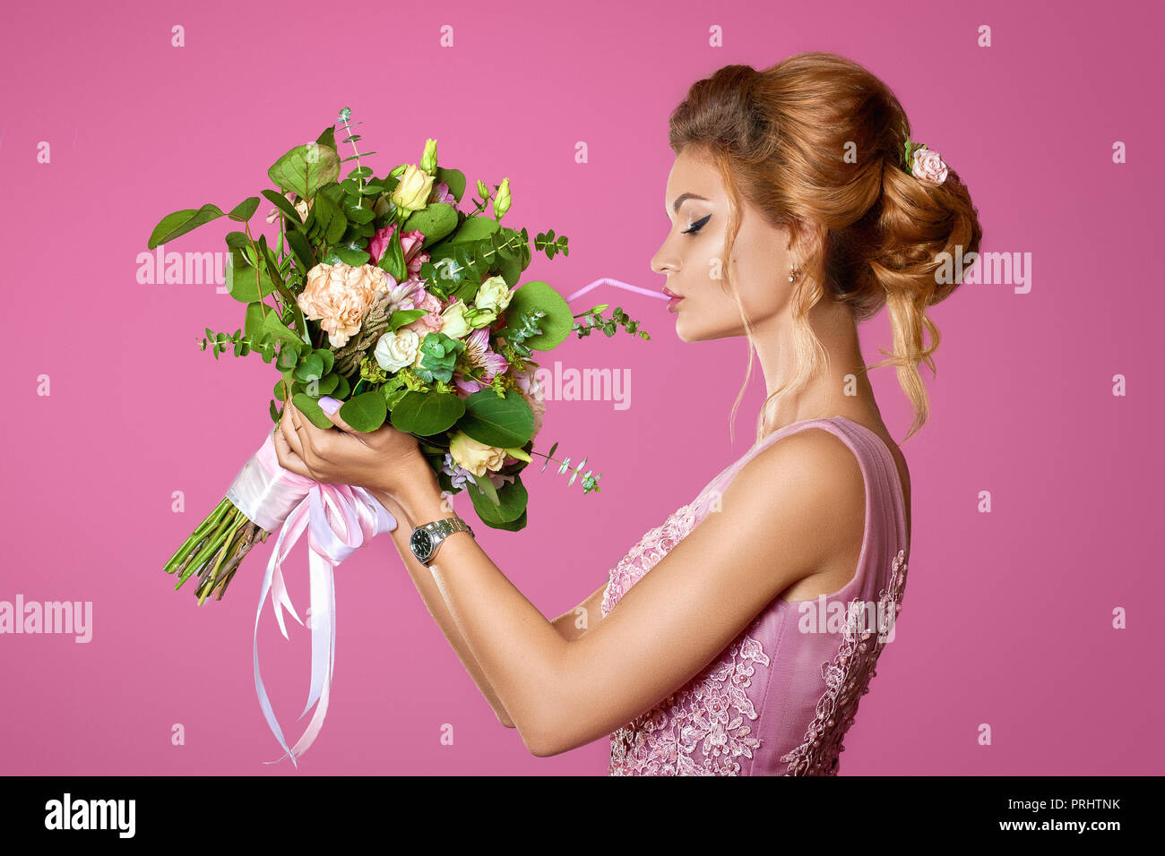 Fashionable model smelling a bouquet flowers on pink background - Stock Image