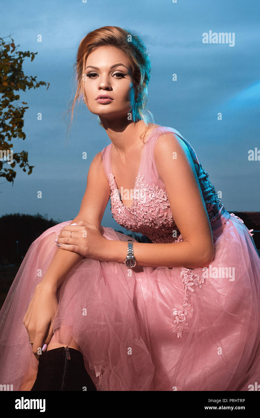 Fashionable model smelling a perfume. Girl in pink dress sitting with makeup and hair in the evening against the sky illuminated by the moon - Stock Image