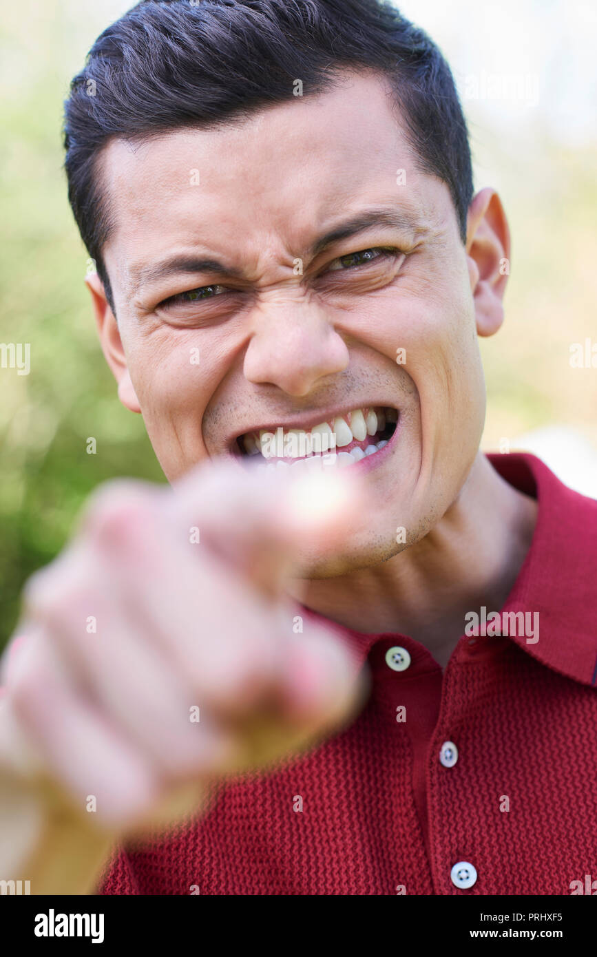 Outdoor Shot Of Angry Young Man Shouting And Pointing At Camera - Stock Image