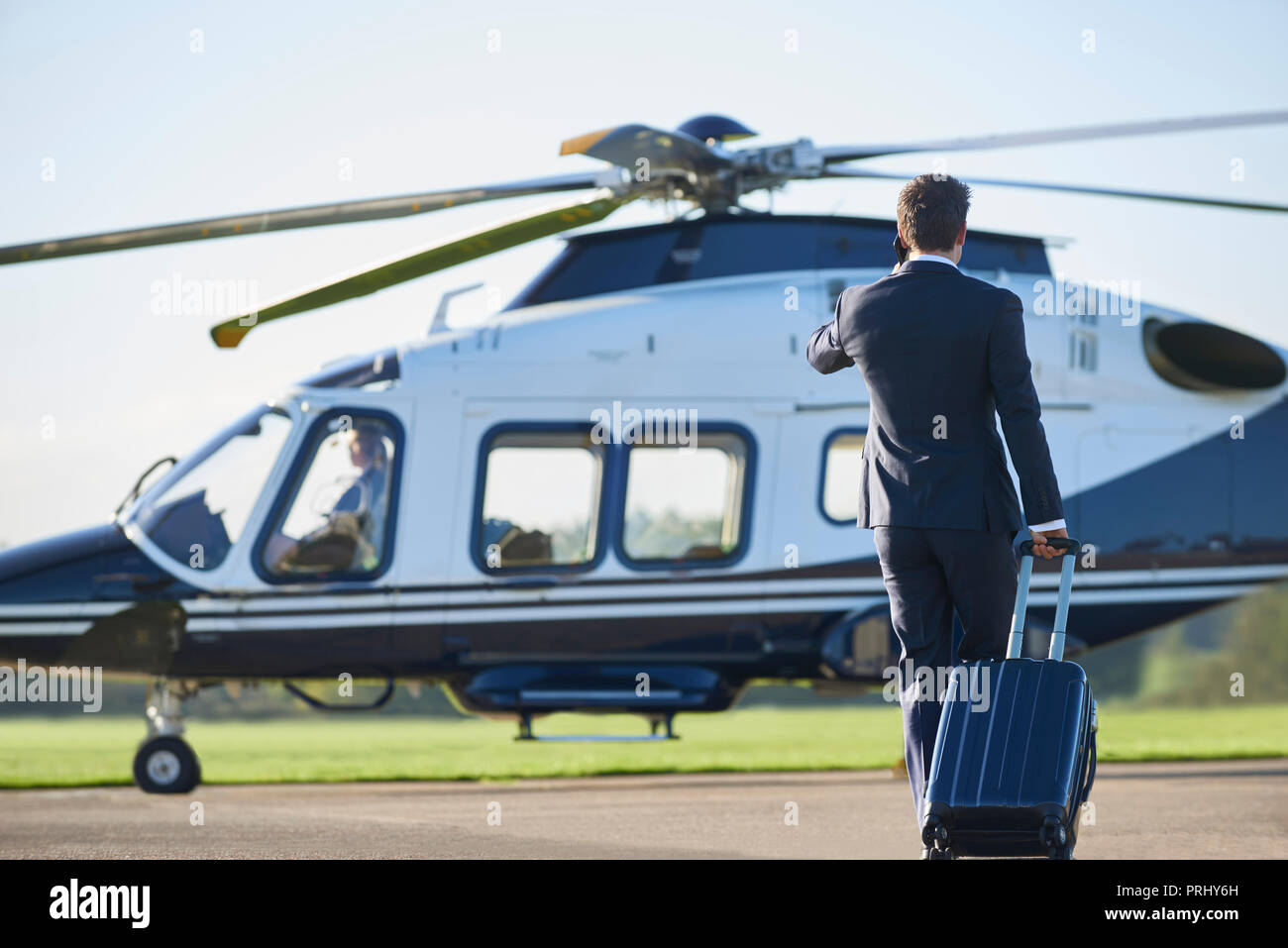Rear View Of Businessman Walking Towards Helicopter Whilst Talking On Mobile Phone - Stock Image
