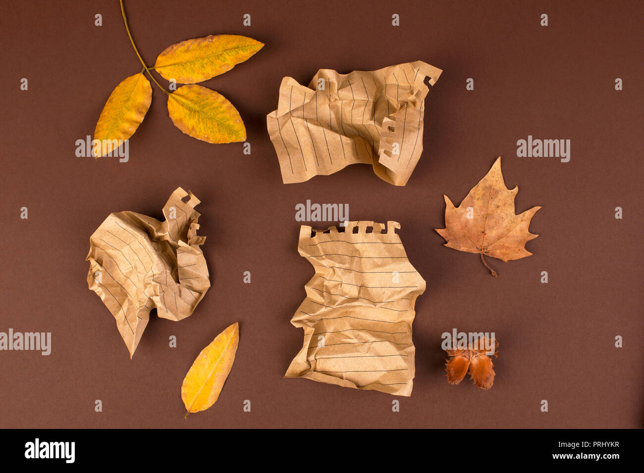 Notepad and crumpled sheets for writing, difficult work to write a letter. Free space for text. Autumn atmosphere and yellow leaves. Top view. Copy space. - Stock Image