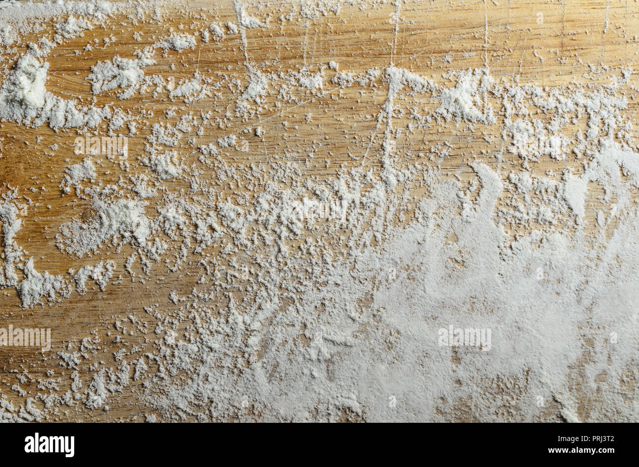 Overhead shot of an old, scratched wooden chopping board, dusted with a sprinkling of white flour. - Stock Image
