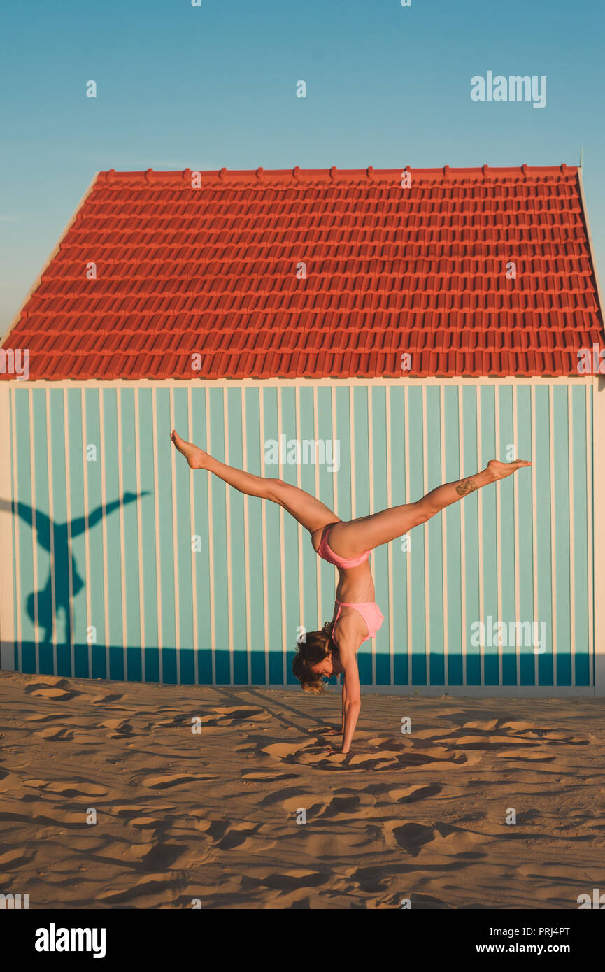 young woman in pink bikini standing on hands against building in Portugal - Stock Image