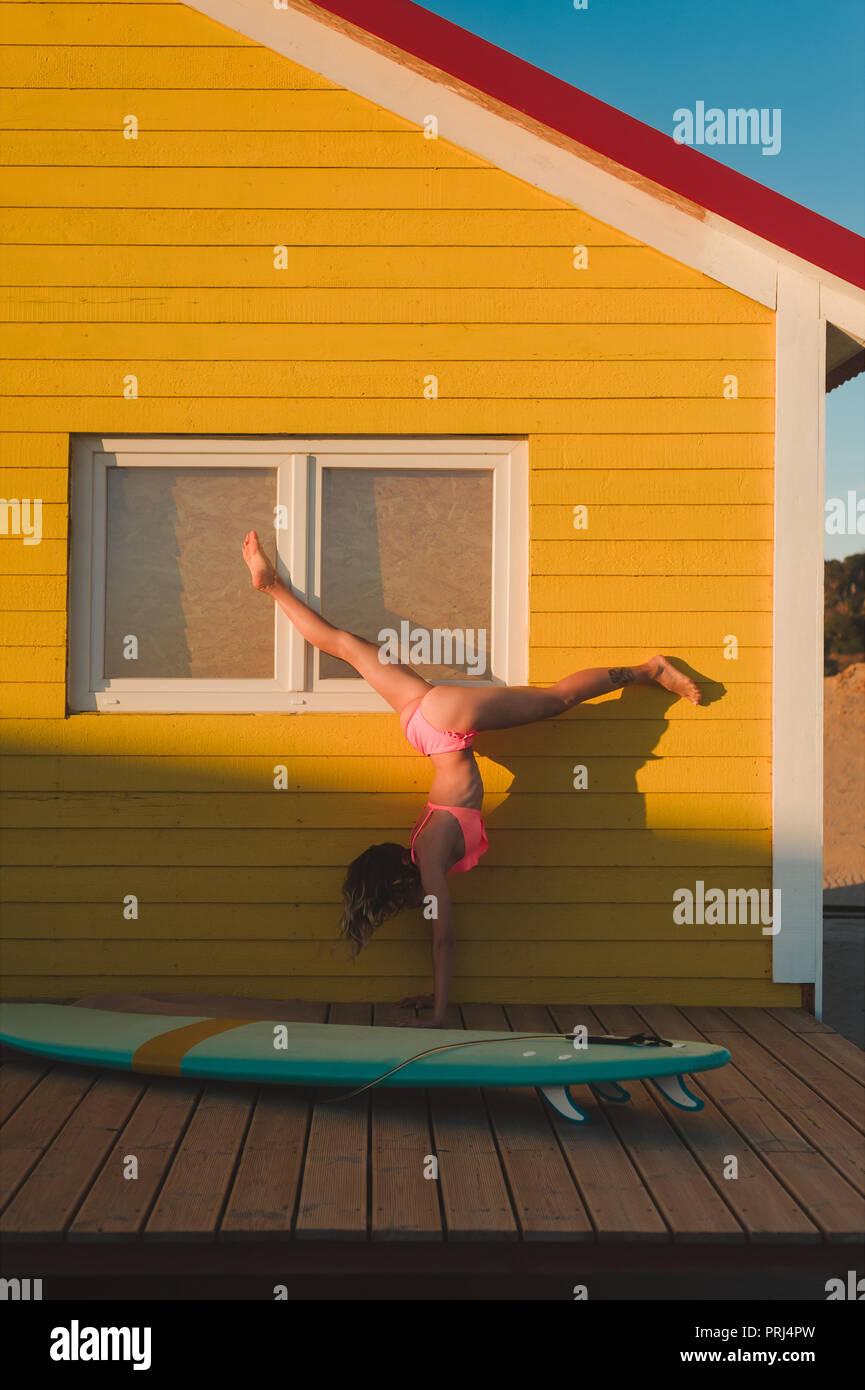 young woman in pink bikini standing on hands against yellow building with surfing board near by in Portugal - Stock Image