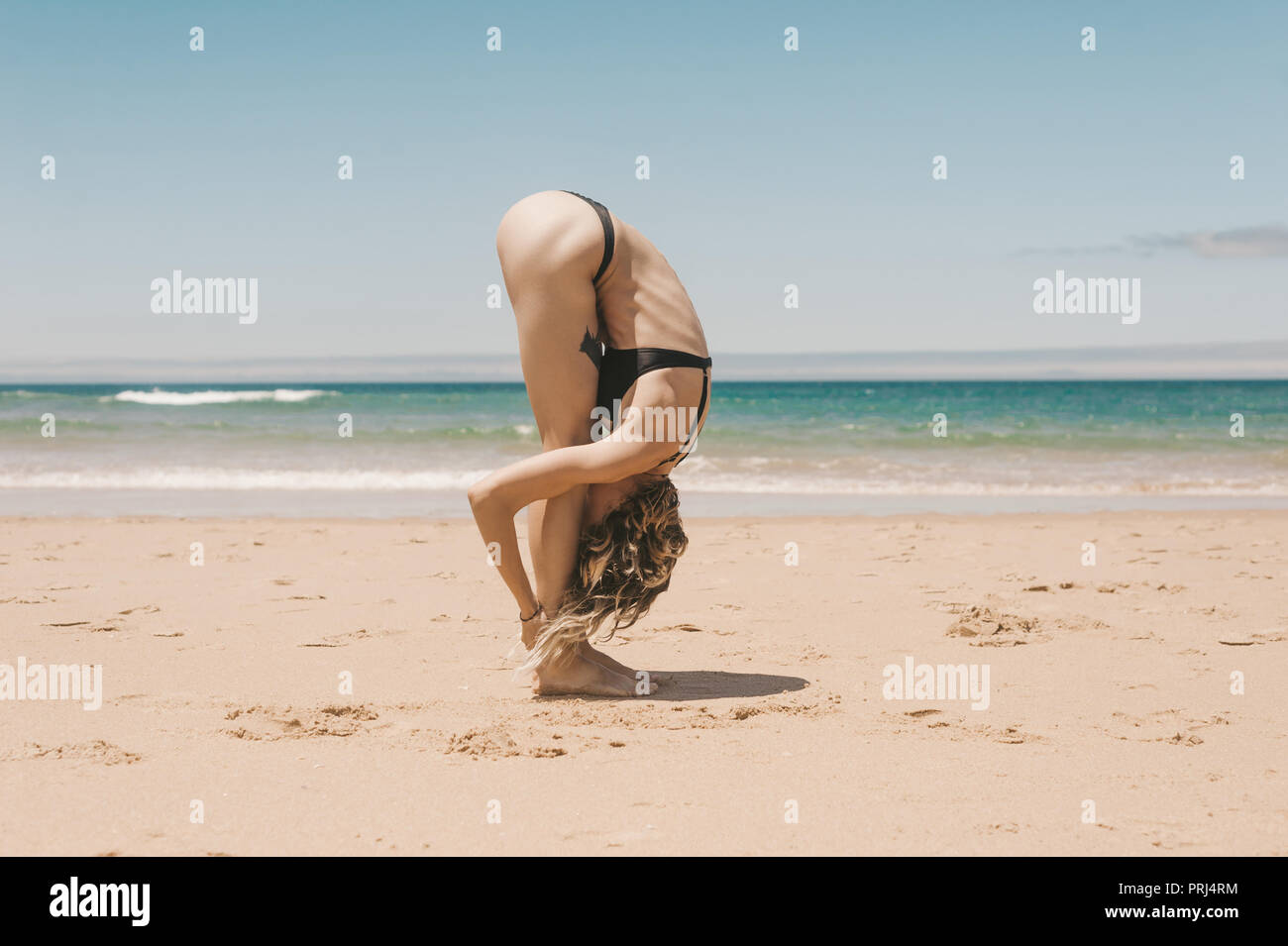 side view of young woman standing in forward fold yoga pose on sandy beach - Stock Image