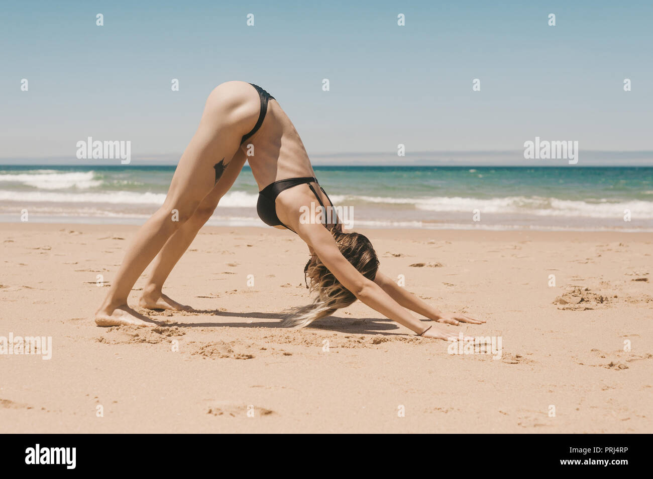 side view of young woman practicing downward facing dog yoga pose on sandy beach - Stock Image