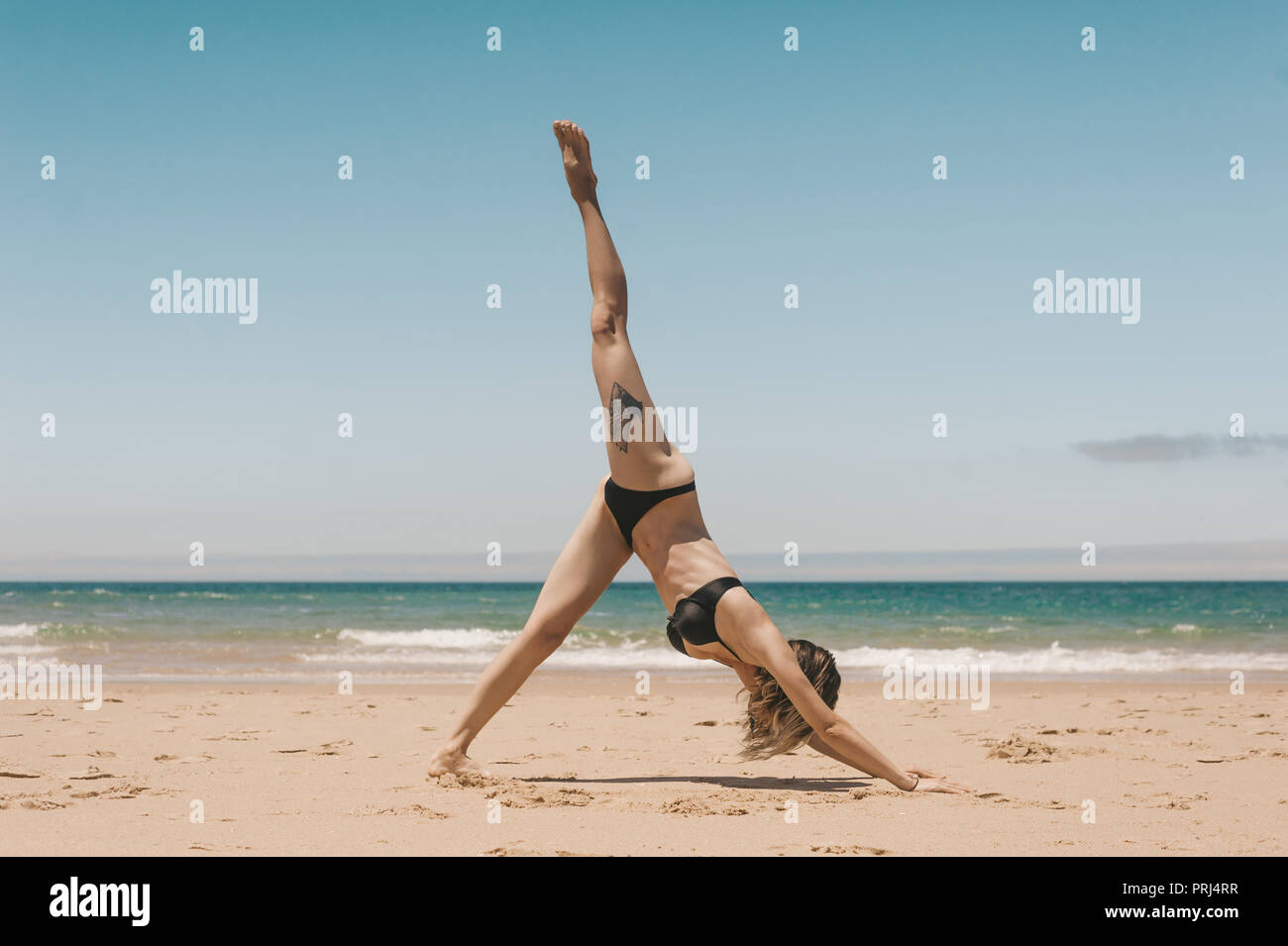 side view of woman practicing downward facing dog yoga pose on sandy beach - Stock Image