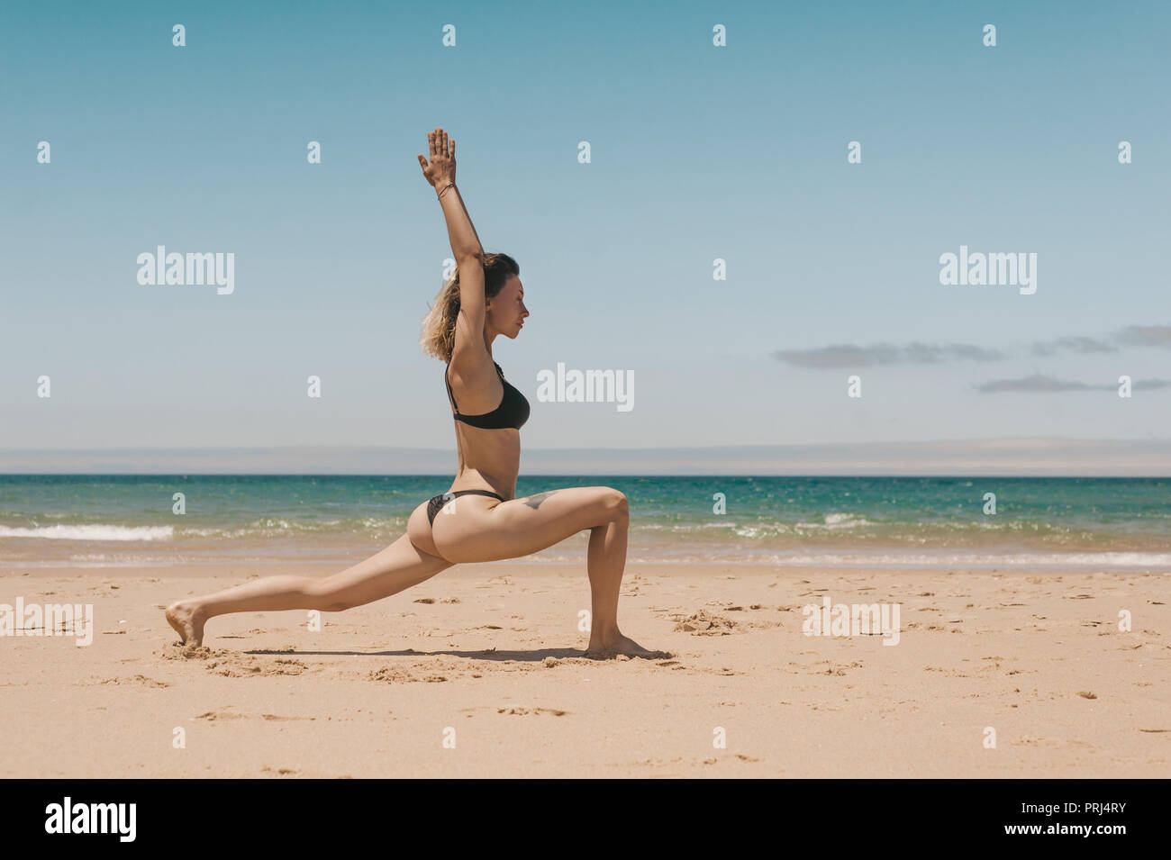 side view of young woman in black bikini standing in Warrior yoga position on sandy beach - Stock Image