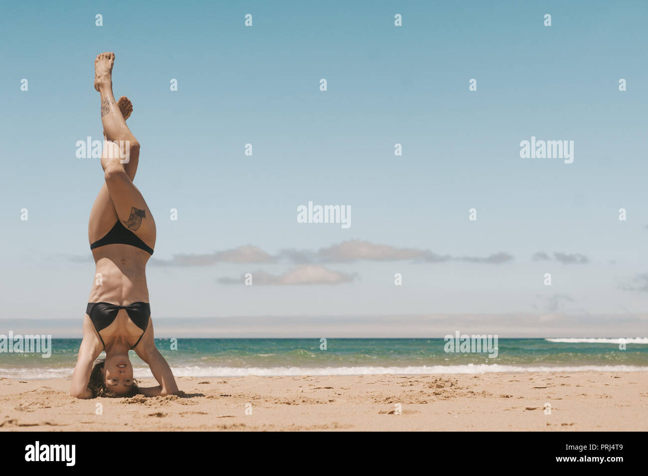young woman practicing headstand on sandy beach on summer day - Stock Image