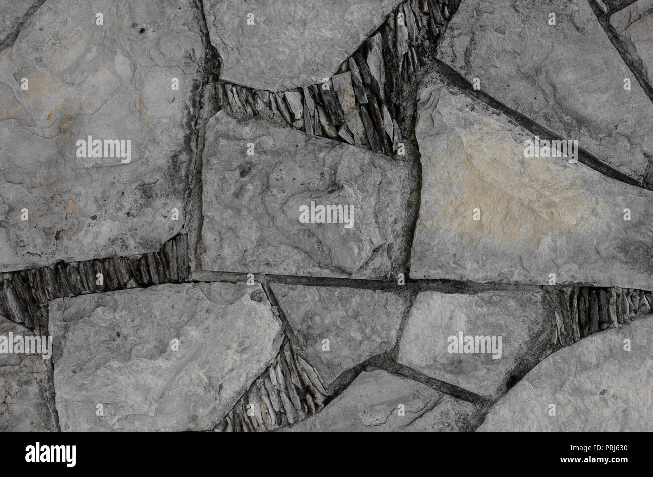 Wall with broken pieces of stones in geometric shapes, natural decorative background. - Stock Image