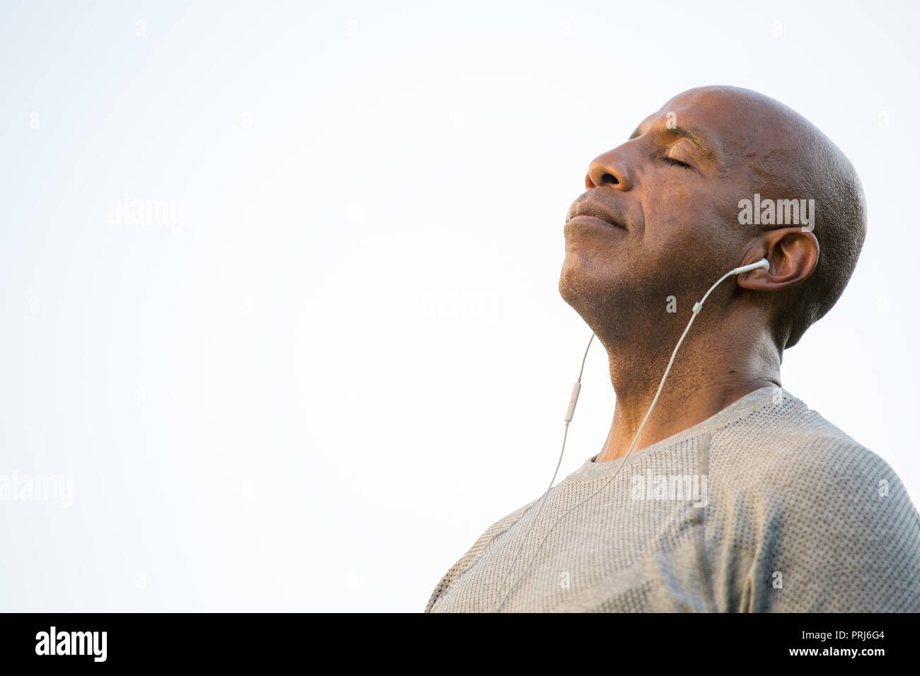 Fit African American man listening to music. - Stock Image