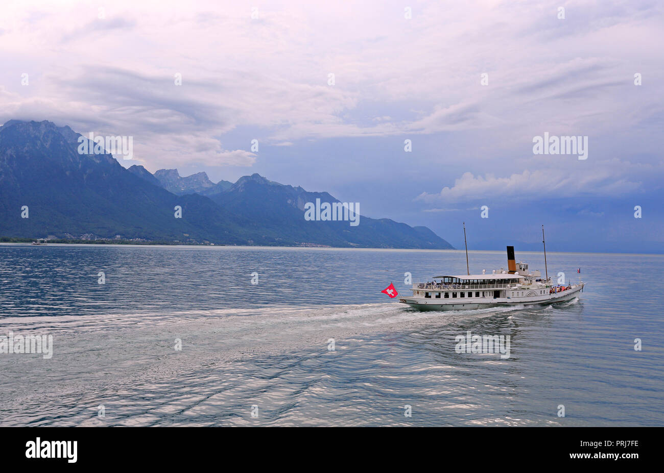 Cruise steamer on Lake Geneva against the background of beautiful mountains and reflection in the water before the storm, Switzerland Stock Photo
