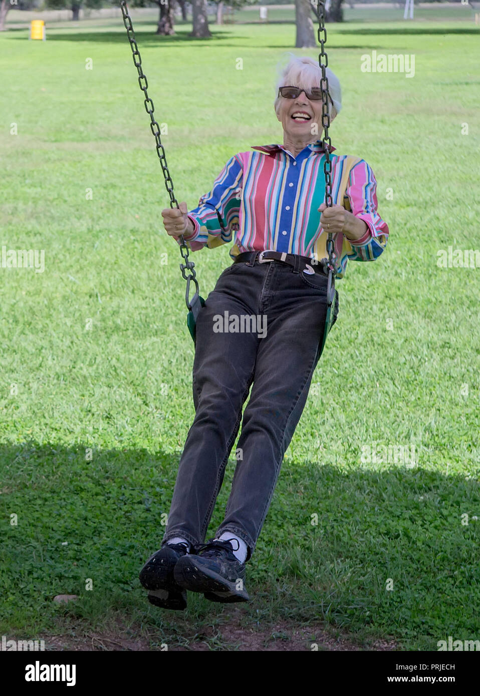 A senior citizen woman enjoying swinging in a public park in far West Texas. - Stock Image