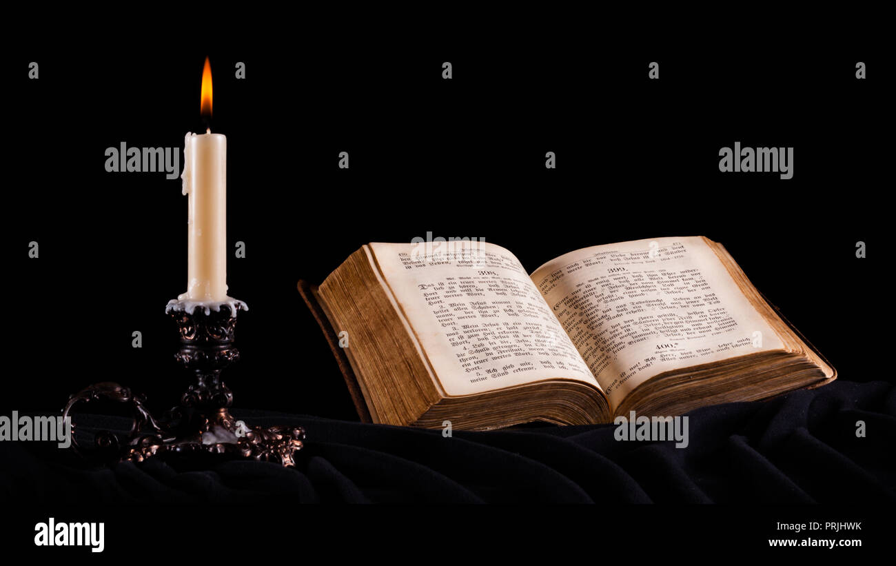 Burning candle and an open old Christian book, stilllife, Germany - Stock Image