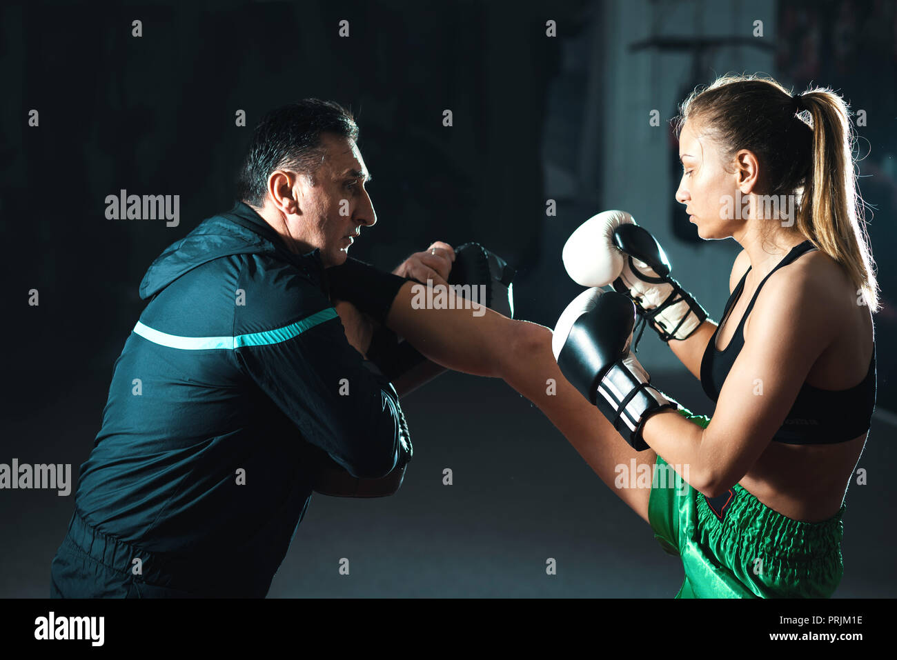 Young adult woman doing high kick during kickboxing training exercise -  Stock Image 6c7f7e89e3