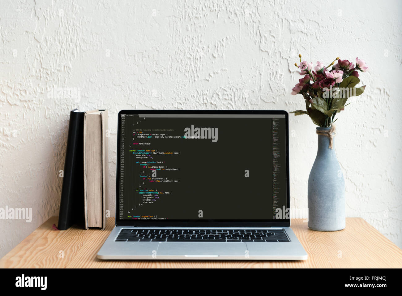 laptop with html code on screen, books and flowers in vase on wooden