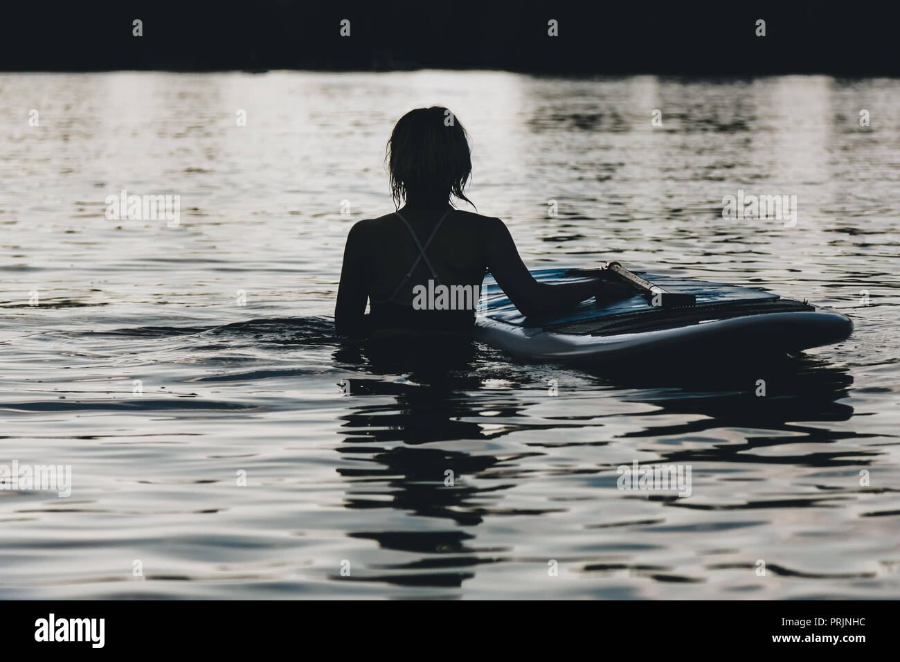 silhouette of woman in water with paddle board - Stock Image