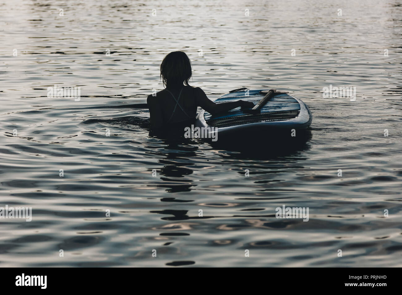 silhouette of woman swimming in water with sup board - Stock Image