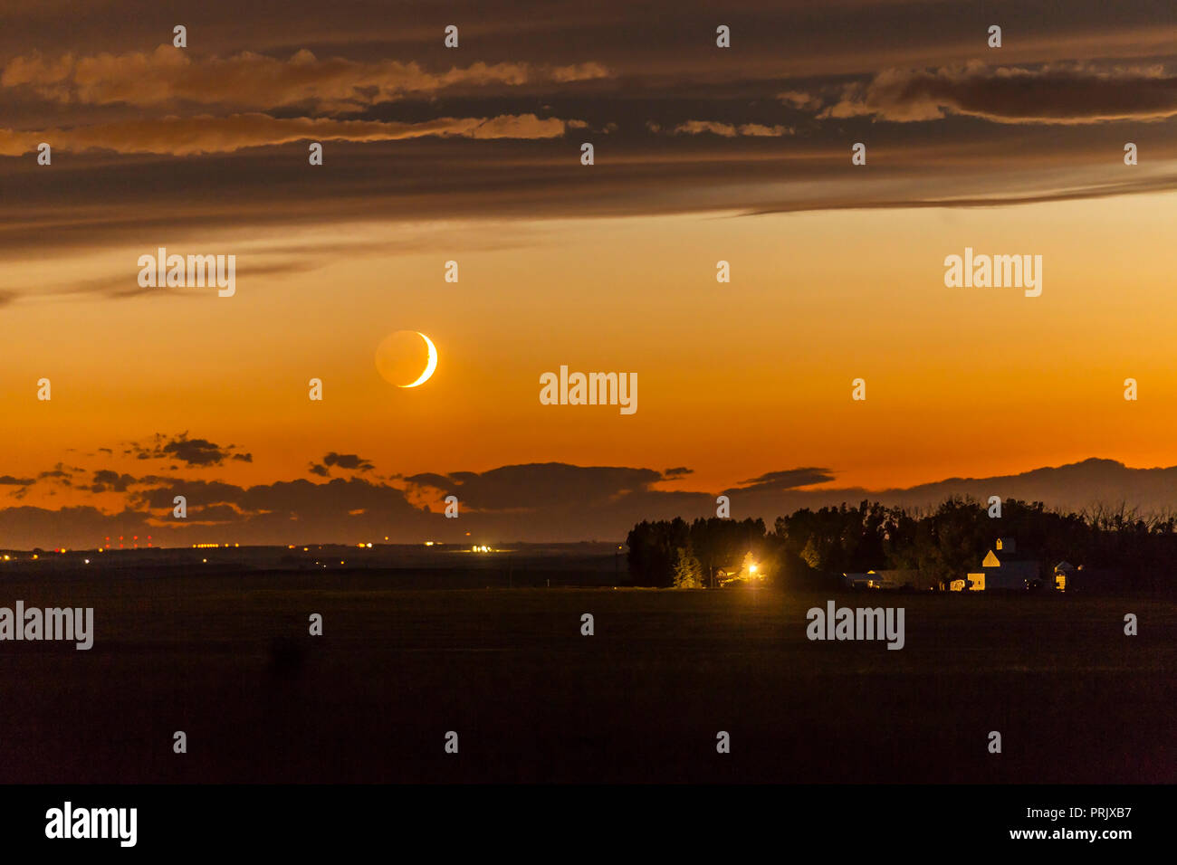 The waxing crescent Moon setting over a nearby farm, on June 26, 2017. Shot at the start of a time-lapse sequence, and shot in haste from home as the  - Stock Image