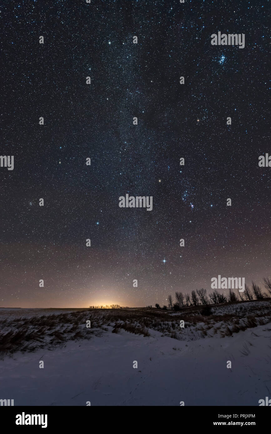 The stars, Milky Way, and constellations of the northern winter sky, including the Winter Hexagon of bright stars, and the Winter Triangle of Betelgeu - Stock Image