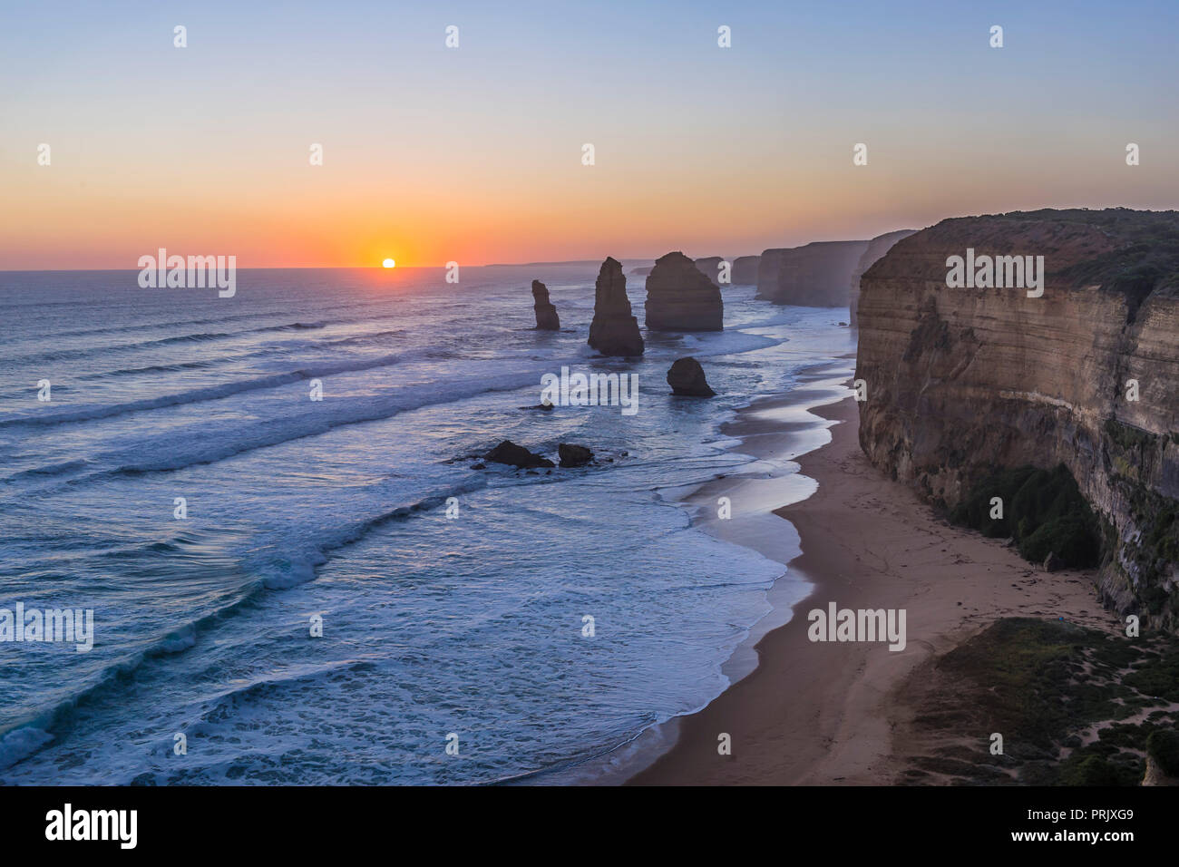 The setting Sun at the Twelve Apostles sea stacks and cliffs on the Great Ocean Road, on April 12, 2017.   This is an HDR stack of 7 exposures from lo - Stock Image
