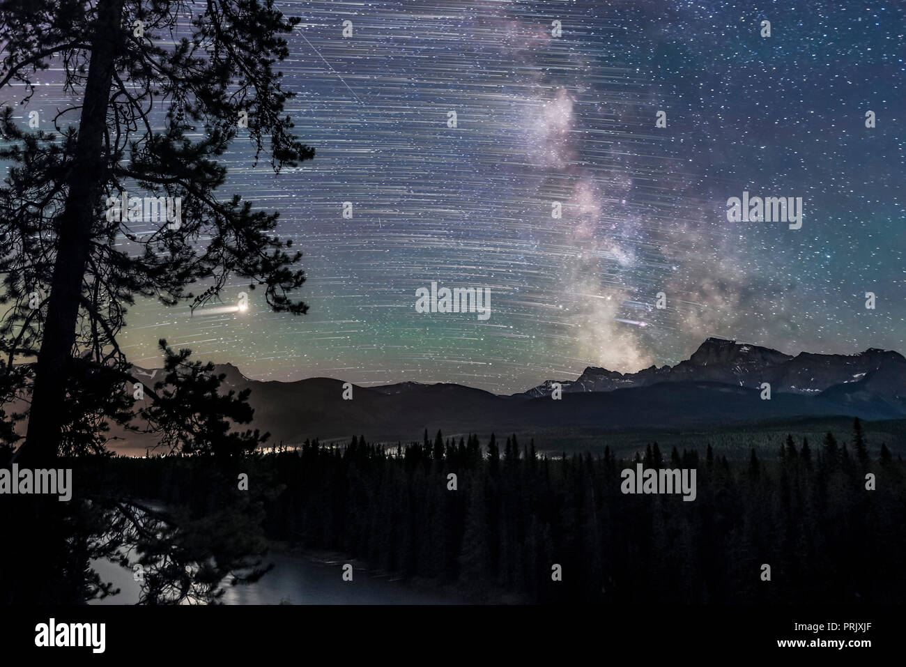 The stars trailing as they move east to west (left to right), ending with the Milky Way and Galactic Centre (right) over Storm Mountain and the Vermil - Stock Image