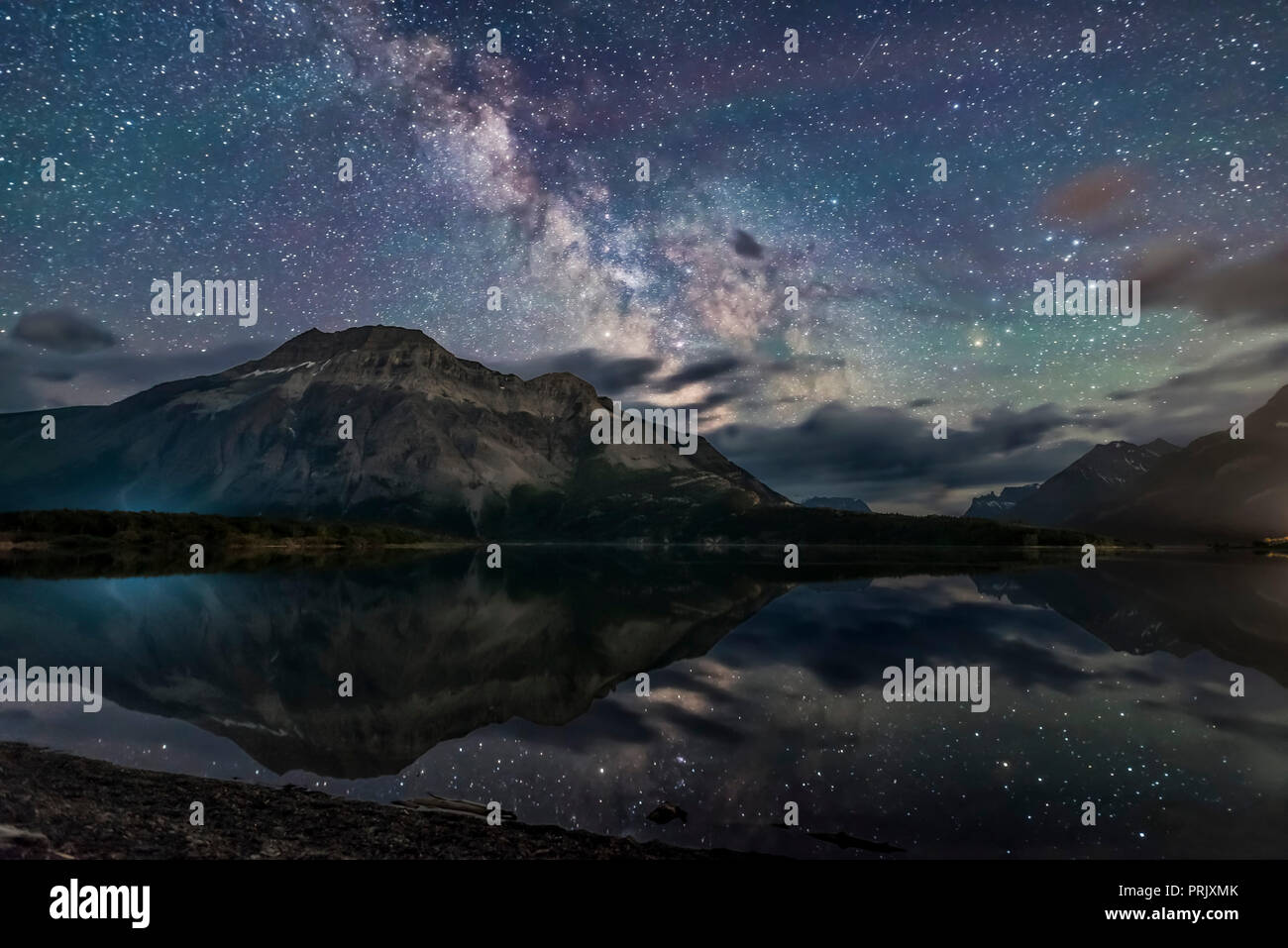 The Milky Way reflected in the unusually calm waters of Middle Waterton Lake from Driftwood Beach, in Waterton Lakes National Park, Alberta, Canada. T - Stock Image