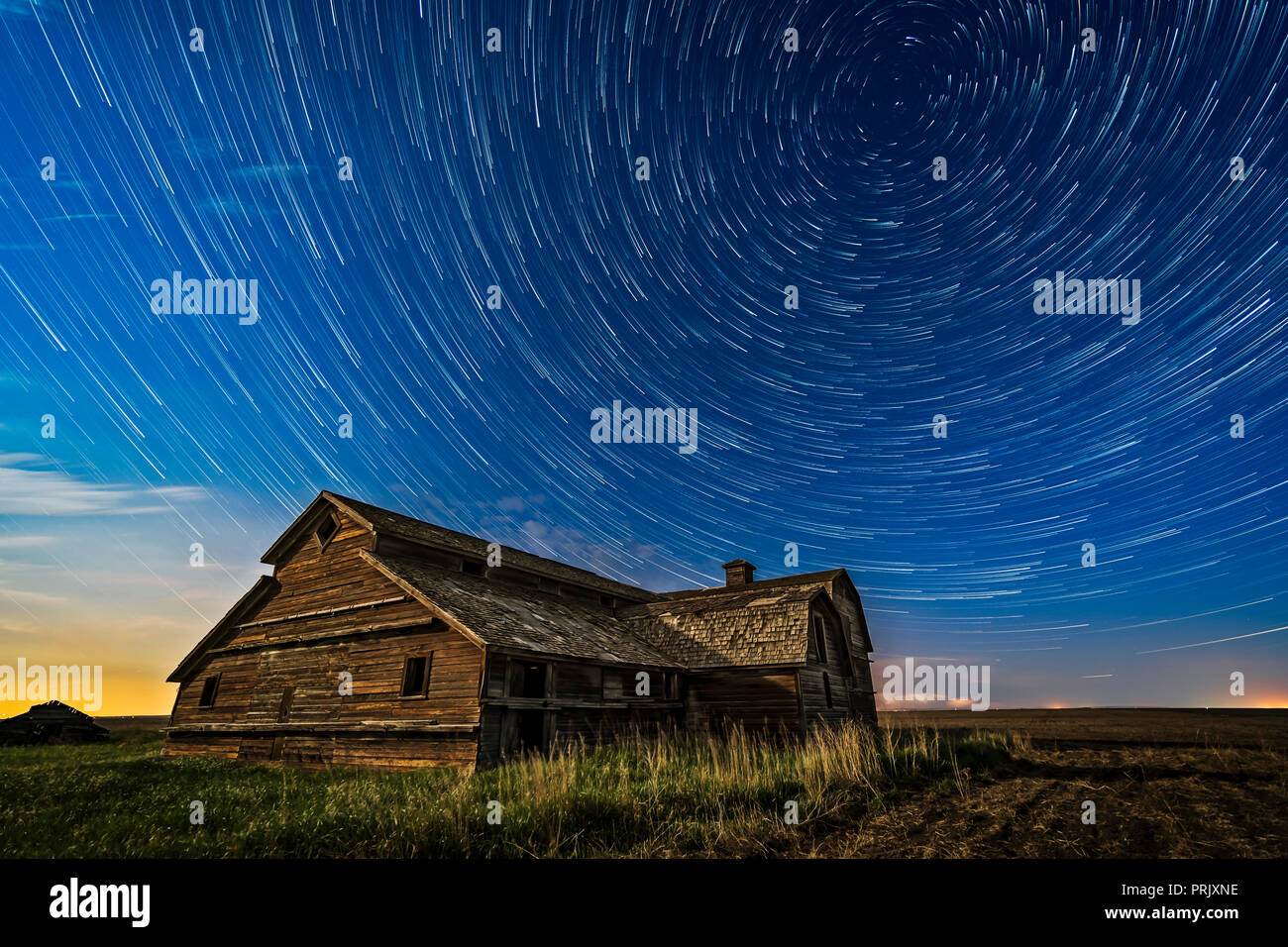 Circumpolar star trails over a grand old barn in southern Alberta, on a fine spring night, May 23, 2018. Illumination is from the waxing gibbous Moon  - Stock Image