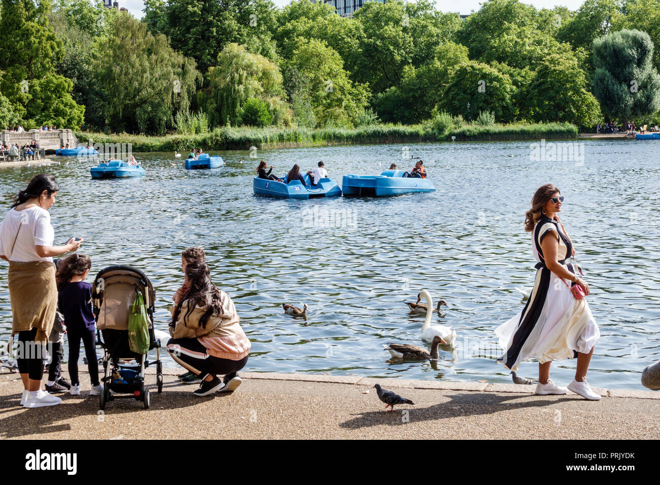 London England United Kingdom Great Britain Royal Parks Hyde Park park green space The Serpentine recreational lake woman girl child family feeding du - Stock Image