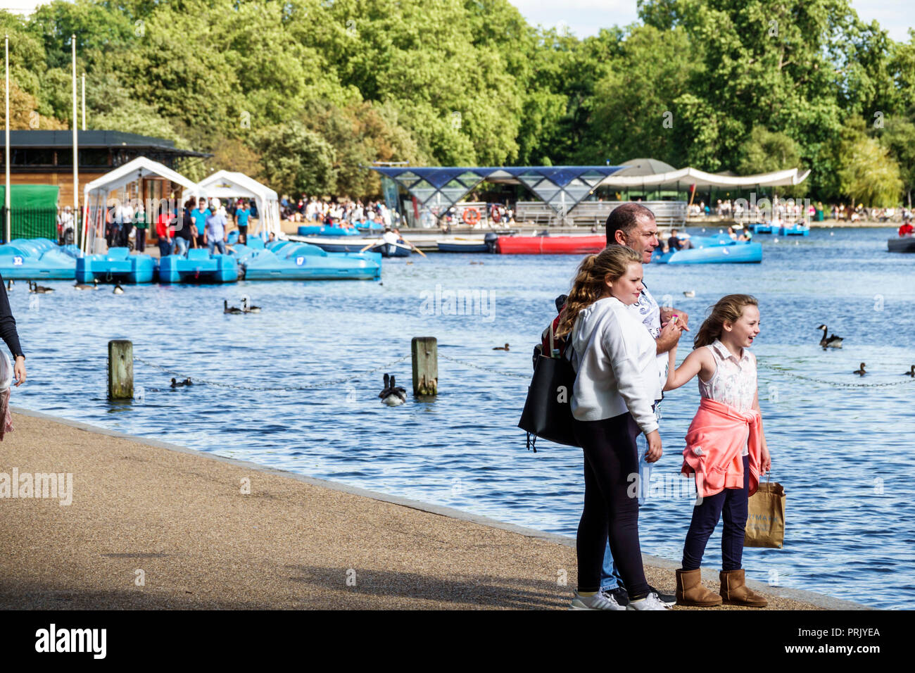London England United Kingdom Great Britain Royal Parks Hyde Park park green space The Serpentine recreational lake man girl teen child family father - Stock Image