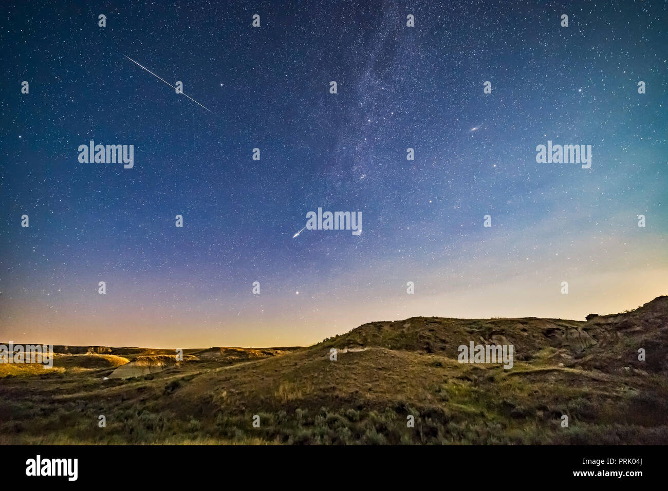 Two bright Perseid meteors (the best two from 3 hours of shooting) over the moonlit landscape of Dinosaur Provincial Park, Alberta, on August 12/13, 2 - Stock Image