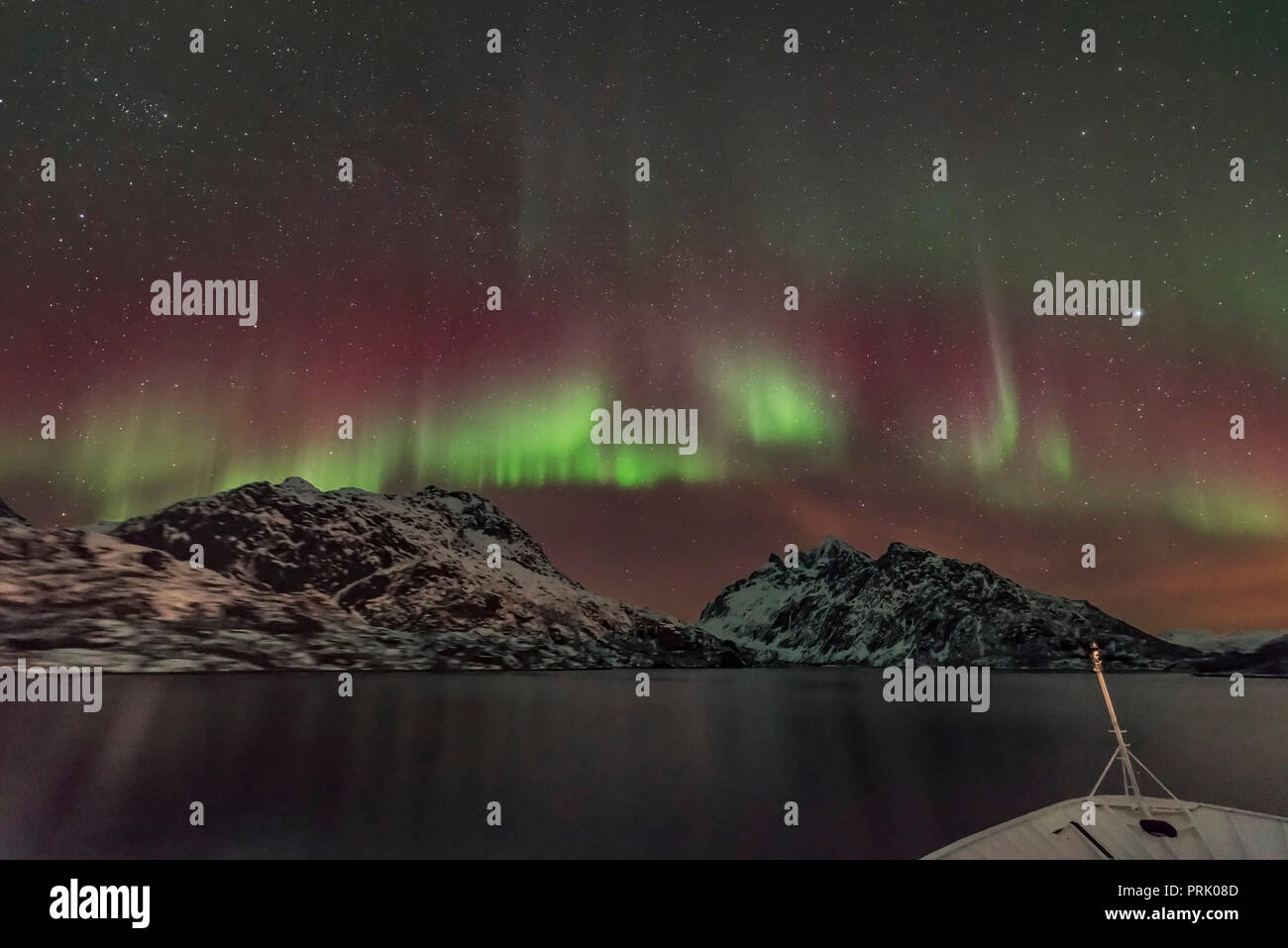 A scene from the Norwegian coast and the Loftoten Islands of the aurora over the entrance to the Trollfjorden fjord, from the forward deck of the Hurt - Stock Image