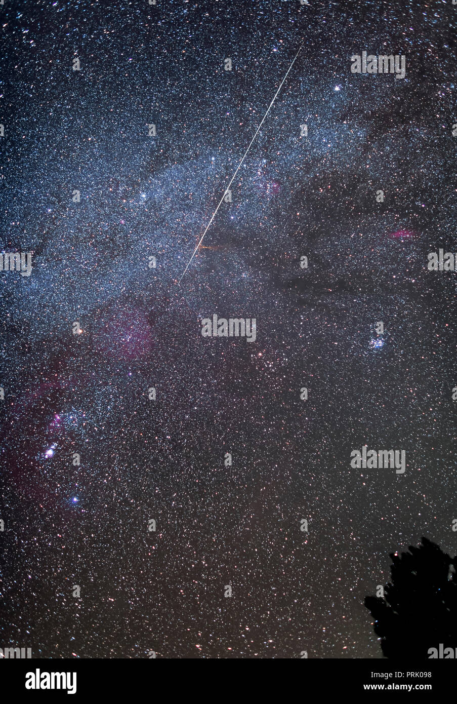 A lone random meteor streaks across the winter Milky Way, and through Auriga and Taurus toward Orion, on December 12, 2017. While this was the night b - Stock Image