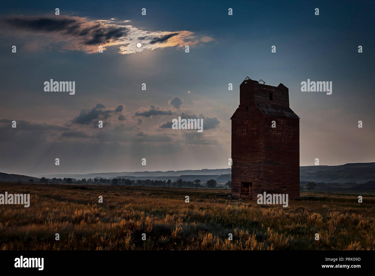 The Full Moon and Mars rising into the southeast over the long abandoned grain elevator at Dorothy, Alberta, in the Red Deer River valley, Alberta. Th Stock Photo