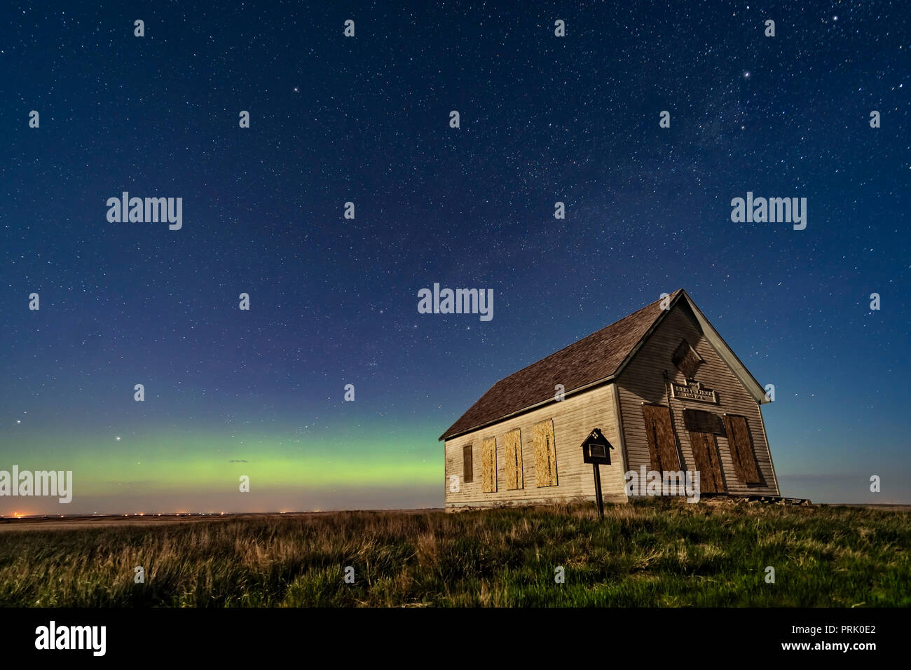 The 1910 Liberty Schoolhouse, a pioneer one-room school, on the Alberta prairie near Majorville, in the moonlight with an aurora across the north. Pol - Stock Image