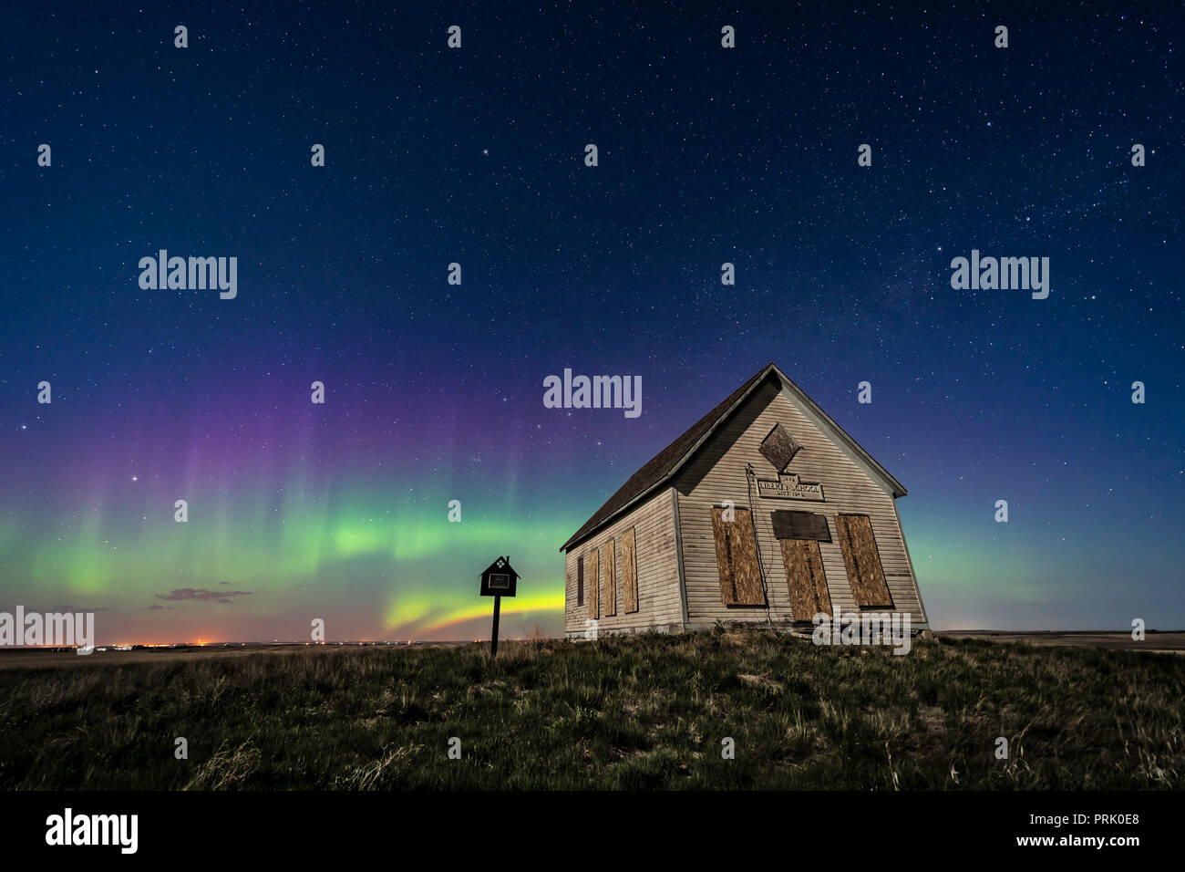 The 1910 Liberty Schoolhouse, a classic pioneer one-room school, on the Alberta prairie under the stars on a spring night, with an aurora dancing to t - Stock Image