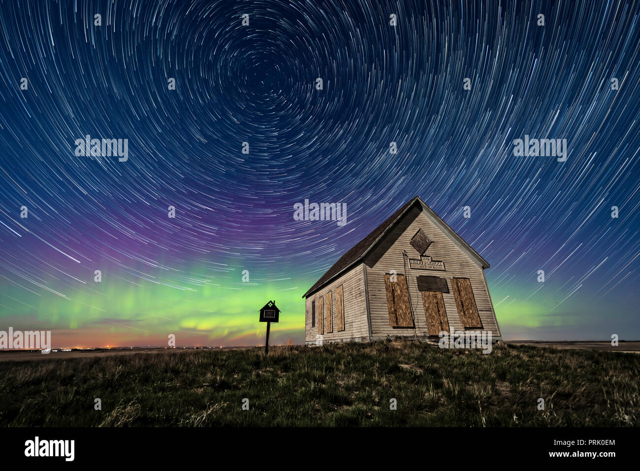 The 1910 Liberty Schoolhouse, a classic pioneer one-room school, on the Alberta prairie under the stars on a spring night, with circumpolar star trail Stock Photo