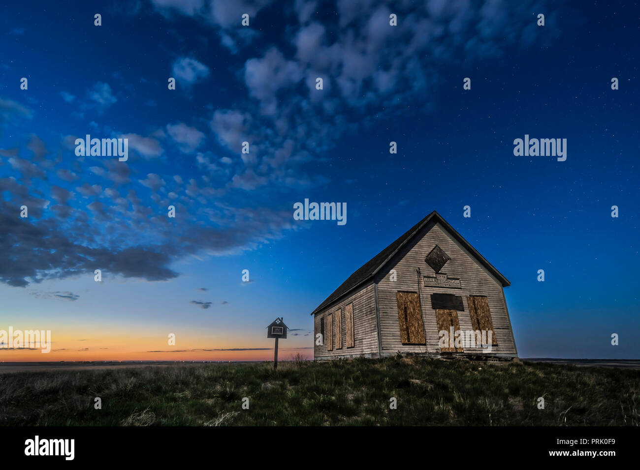 The 1910 Liberty Schoolhouse, a classic pioneer one-room school, on the Alberta prairie under the stars in the twilight of a spring night. Moonlight f - Stock Image