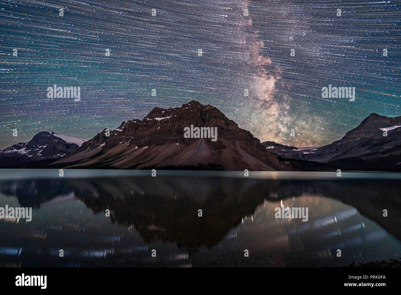A blend of images to show the stars of the southern sky moving from east to west (left to right) over the Rocky Mountains at Bow Lake, in Banff, Alber - Stock Image