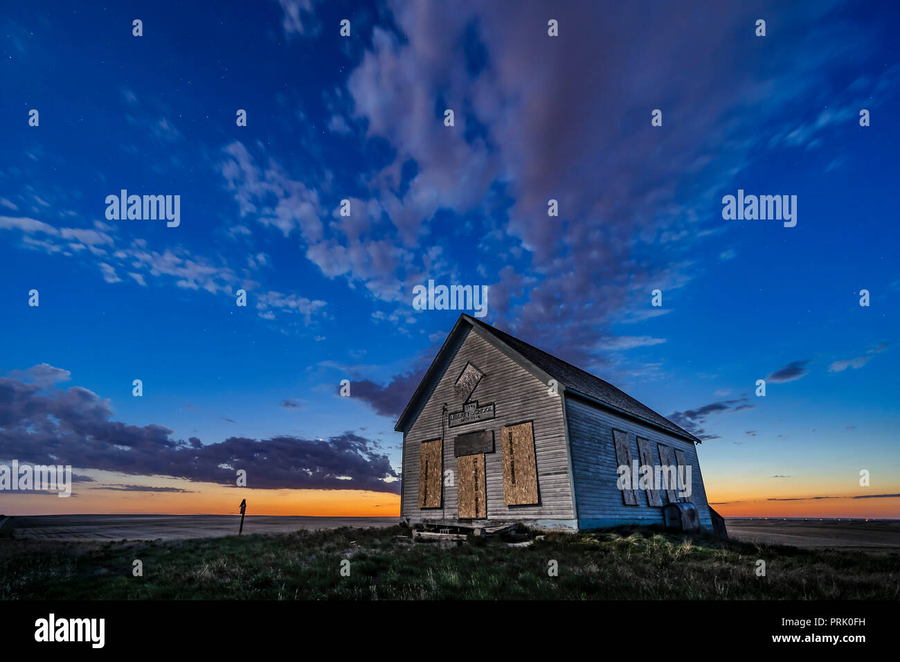 The 1910 Liberty Schoolhouse, a classic pioneer one-room schoolhouse on the Alberta prairie, at sunset as the stars are appearing, and with Venus in t Stock Photo