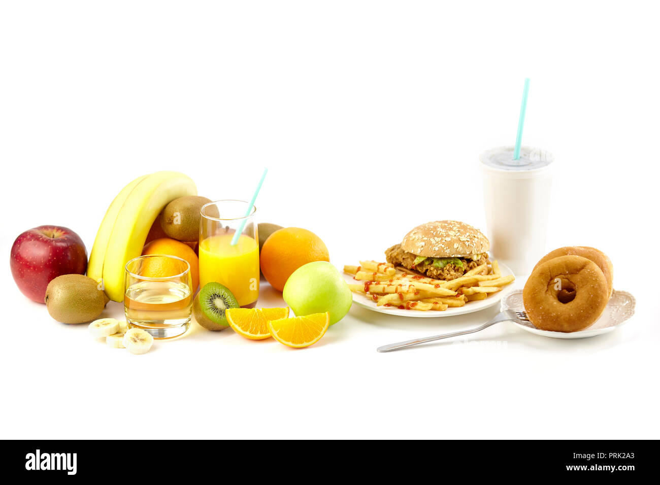assorted fresh fruits, juice, hamberger, french fries, doughnuts and soft drink isolated on white background. Stock Photo