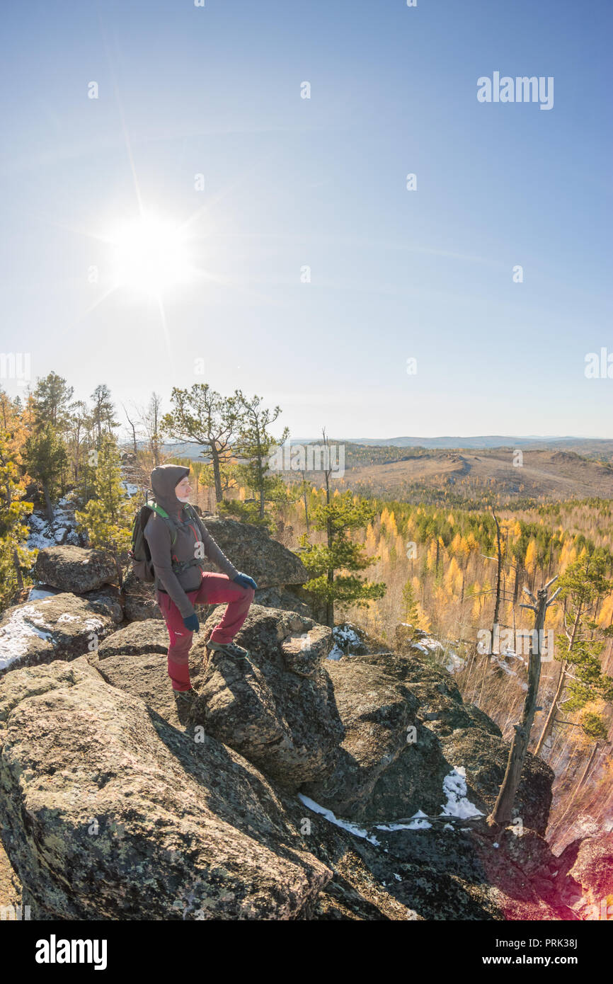 Woman with backpacks standing on a rock in autumn forest - Stock Image