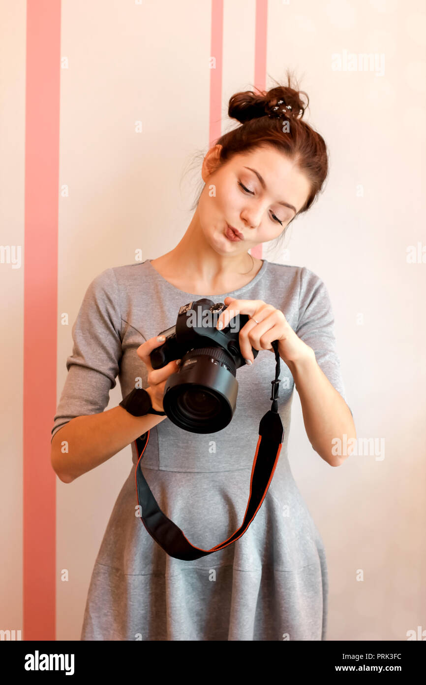 Pretty girl photographer looks into her camera and makes funny f - Stock Image