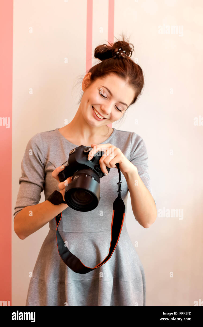 Portrait of young woman photographer smiling and holding her cam - Stock Image